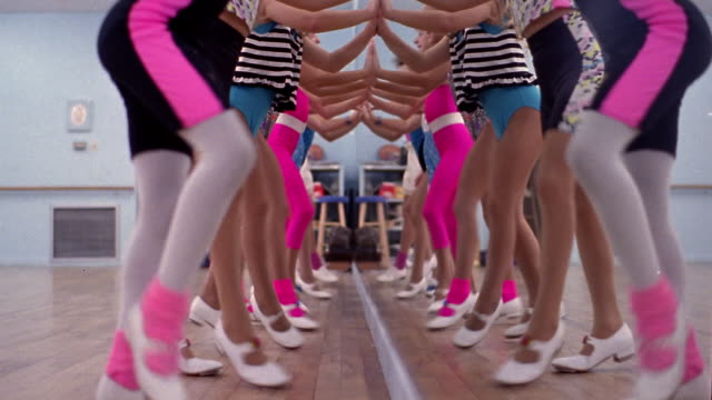1980s slow motion low angle close up legs of girls tap dancing in a line with hands pressed to mirror / dallas, texas - lycra stock-videos und b-roll-filmmaterial