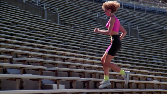 1980s slow motion medium shot tracking shot woman running up bleachers in stadium - lycra stock-videos und b-roll-filmmaterial