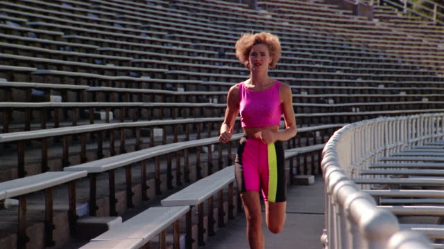 1980s slow motion medium shot woman running towards CAM on bleachers in stadium