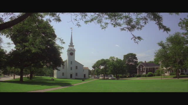 1980s ws small new england colonial style church with tall steeple and dogs running on lawn - steeple stock videos & royalty-free footage