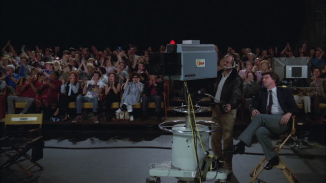 vídeos de stock, filmes e b-roll de 1980s ws television studio with audience clapping, camera man in foreground - ateliê