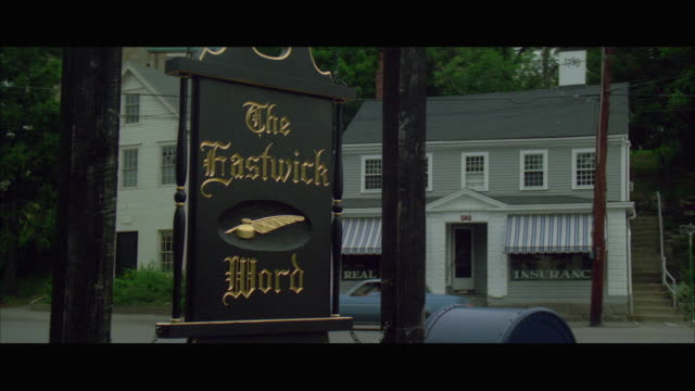 stockvideo's en b-roll-footage met 1980s ws the eastwick word sign on newspaper office in small town with background traffic - literatuur