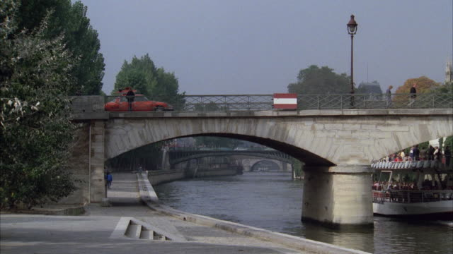 1980s ws zo pan traffic on bridge and tourboat on seine river by notre dame cathedral / paris, france - besichtigung stock-videos und b-roll-filmmaterial
