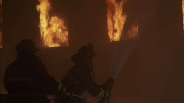 stockvideo's en b-roll-footage met 1980s ms two firemen fighting fire burning in large building - fire hose