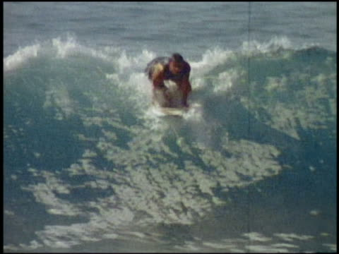 1980s wide shot tracking shot surfer riding wave in t shirt, swimming trunks, and socks / california - 1980 stock videos and b-roll footage