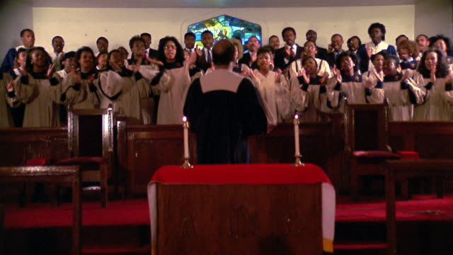 stockvideo's en b-roll-footage met 1980s wide shot zoom in gospel choir clapping and swaying + singing in church / director's back to cam / houston - kerk