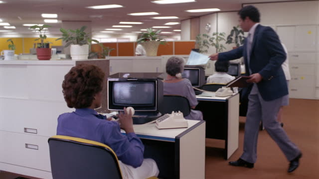 vidéos et rushes de 1980s ms women working, talking on telephones, and typing on old-fashioned computers in office / new orleans, louisiana, usa - historique