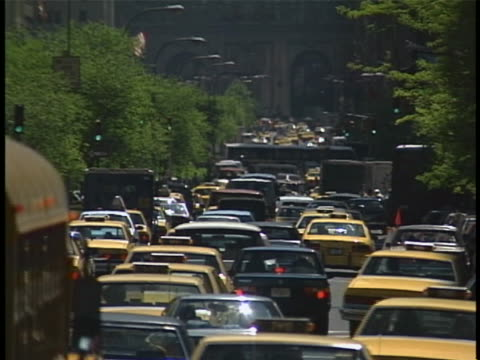 1990s cars, school buses and yellow cabs try to maneuver through traffic in new york city, 1991. - gelbes taxi stock-videos und b-roll-filmmaterial