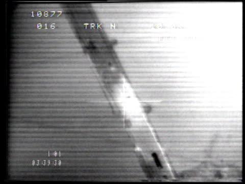 1990s ws crosshairs targeting vehicles on road beneath aircraft in flight then target exploding / kuwait - fadenkreuz stock-videos und b-roll-filmmaterial