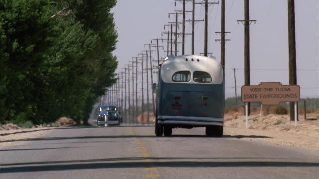 stockvideo's en b-roll-footage met 1990s ws traffic on rural highway - westers schrift