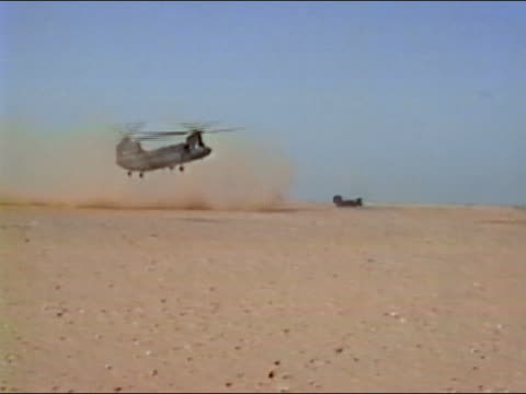 1990s wide shot military helicopter landing in desert / sand blowing around / desert storm / audio - wide shot stock videos & royalty-free footage