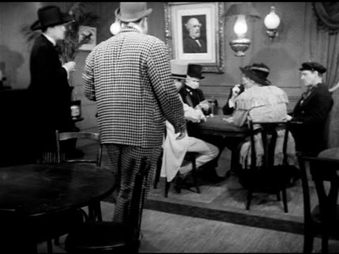 19th century gamblers: man in checkered suit w/ beer watching poker game from table, 'jack o'diamonds' standing bg, man walking over to game trying... - hand of cards stock videos & royalty-free footage