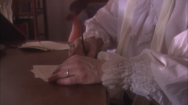 A 19th century scribe sits at a desk writing with a quill pen.
