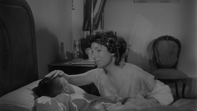 vidéos et rushes de 19th century setting, woman enters a room and checks on boy. - 1960