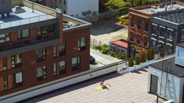 stockvideo's en b-roll-footage met 19-jarig meisje dat geschiktheidsoefeningen op een dak voor een afgelegen mening aan manhattan doet - zitting en het uitrekken van haar rug en handen. - 18 19 years