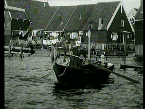 vídeos de stock, filmes e b-roll de 1jan1923 b/w montage adults and children in traditional costume getting around in rowboats during floods / marken netherlands - 1923