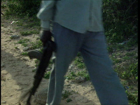oct-1998 armed militiamen walking past camera / mogadishu, benadir, somalia - 30代の男性だけ点の映像素材/bロール