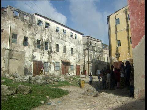 vídeos de stock e filmes b-roll de oct-1998 crowd of people standing outside war damaged apartment buildings / mogadishu, benadir, somalia - corno de áfrica