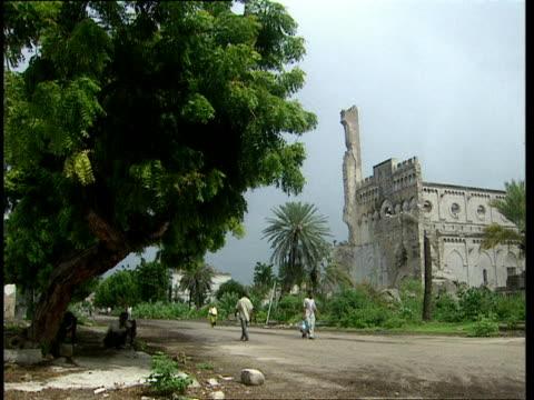 vídeos de stock e filmes b-roll de oct-1998 few pedestrians walking down quiet dirt road past ruins of buildings damaged by war / mogadishu, benadir, somalia - corno de áfrica