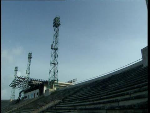 vídeos de stock e filmes b-roll de oct-1998 light towers and empty seats and overgrown playing field inside mogadiscio stadium / mogadishu, benadir, somalia - corno de áfrica