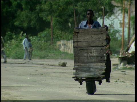 oct-1998 man walks pushing empty makeshift rickshaw / mogadishu, benadir, somalia - rikscha stock-videos und b-roll-filmmaterial