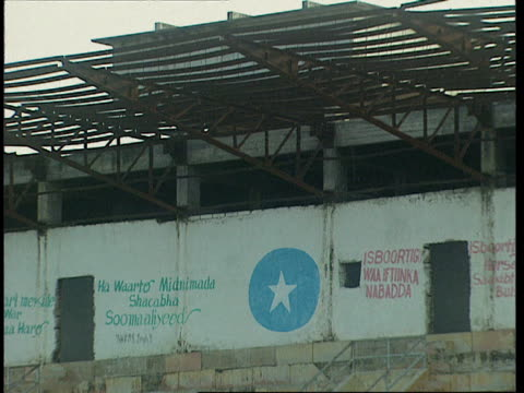 1oct1998 montage graffiti on walls behind seating in abandoned mogadiscio stadium / mogadishu benadir somalia - western script stock videos & royalty-free footage