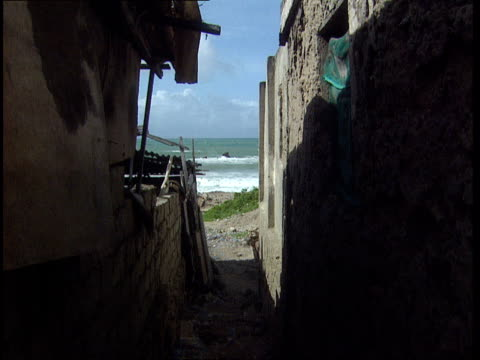 vidéos et rushes de oct-1998 narrow alley between damaged houses with waves crashing on somali coast / mogadishu, benadir, somalia - moins de 10 secondes