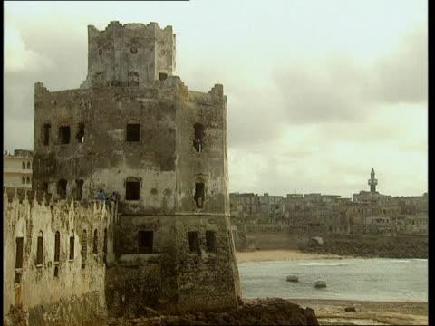 vídeos de stock e filmes b-roll de oct-1998 old battered mogadishu lighthouse stands along bay, mogadishu skyline in background / mogadishu, benadir, somalia - corno de áfrica