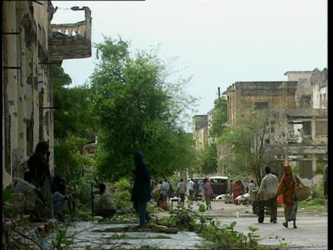 vídeos de stock e filmes b-roll de oct-1998 pedestrians in street bordered by damaged buildings and ruins / mogadishu, benadir, somalia - corno de áfrica