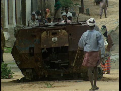 vídeos de stock e filmes b-roll de oct-1998 pedestrians passing remains of armored vehicle left in road / mogadishu, benadir, somalia - corno de áfrica