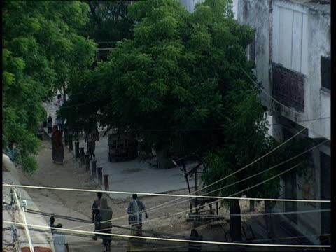 vídeos de stock e filmes b-roll de oct-1998 pedestrians walking in street near us army rangers black hawk helicopter crash site / mogadishu, benadir, somalia - corno de áfrica