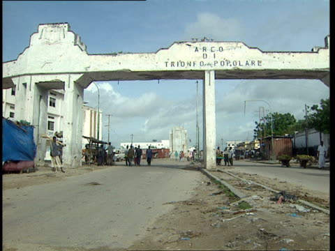 1oct1998 ws pedestrians walking through arco di trionofo popolare people's arch that spans via makaalmukara / mogadishu benadir somalia - western script stock videos & royalty-free footage