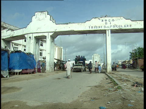 vidéos et rushes de 1oct1998 ws pedestrians walking through arco di trionofo popolare people's arch that spans via makaalmukara / mogadishu benadir somalia - écriture européenne