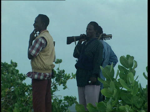 1oct1998 ms three men standing in field one has rocket propelled grenade launcher / mogadishu benadir somalia - only mid adult men stock videos & royalty-free footage