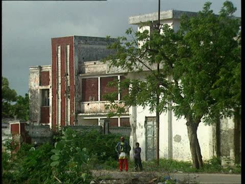 vídeos de stock e filmes b-roll de oct-1998 two young people standing in front of damaged buildings, bus passing / mogadishu, benadir, somalia - corno de áfrica