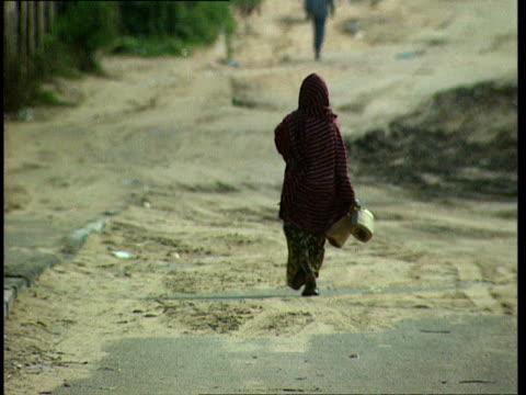 1oct1998 ws woman walking in street with empty water jugs / mogadishu benadir somalia - milk churn stock videos & royalty-free footage