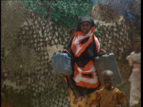vidéos et rushes de oct-1998 women and children in brightly colored scarves in village. one woman walks through carrying water jugs / mogadishu, benadir, somalia - couvre chef
