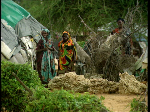 vidéos et rushes de oct-1998 women in brightly colored scarves outside of dome shaped homes in village / mogadishu, benadir, somalia - couvre chef
