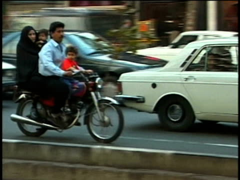 1st april 2000 ws pan family riding on motorbike down khomeini avenue / tehran, iran - iran stock-videos und b-roll-filmmaterial