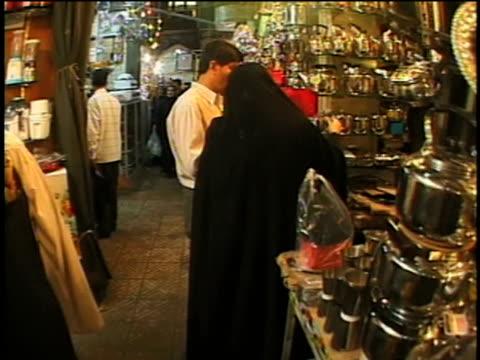 vídeos de stock, filmes e b-roll de 1st april 2000 ms pov men and women shopping in very busy alley of tehran bazaar. / tehran, iran - antiquário loja