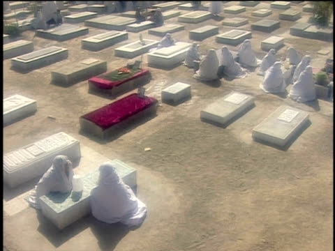 1st March 2000 WS HA Women in white veils visiting graves in cemetery / Varzaneh, Ispahan, Iran
