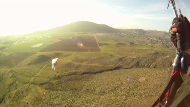 1st person pov of glider watching friend soar below him - paragliding stock videos & royalty-free footage