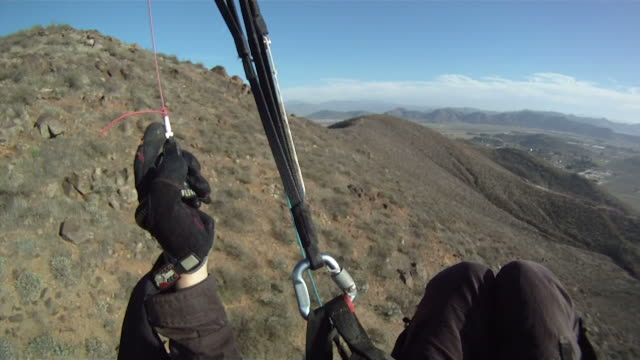 1st person pov of paraglider flying alongside a mountain - paragliding stock videos & royalty-free footage