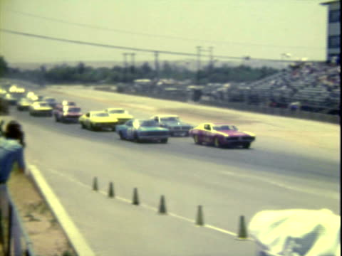 20Jun1971 MONTAGE Stock cars lined up in pit alley at Riverside International Raceway / PAN MS driver Richard Petty wearing sunglasses racing suit...