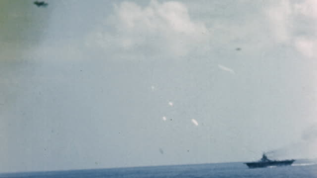 20mm and 40mm tracer rounds and flak bursts fired at japanese fighter plane, and plane crashing into the water near battleship underway in the... - 日本の軍事力点の映像素材/bロール