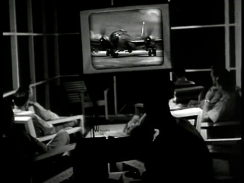 INT 20th Air Force projection room w/ officers watching footage of B29 'Superfortress' taxiing General Curtis LeMay seated CU General Curtis LeMay...