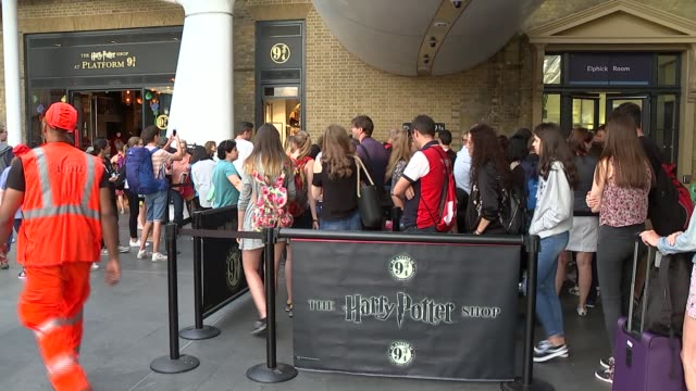 stockvideo's en b-roll-footage met 20th anniversary of publication of the first harry potter book gvs of tourists at platform 9 3/4 england london king's cross station int sign on wall... - station london king's cross
