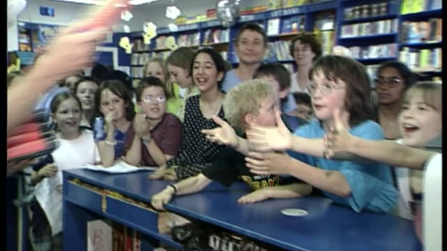 20th anniversary of publication of the first harry potter book; bsp080799067 / 8.7.1999 london: various of children getting excited in bookshop as... - jahrestag stock-videos und b-roll-filmmaterial