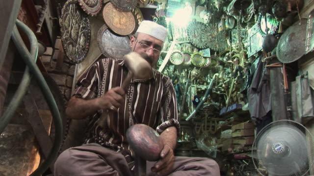 vídeos de stock e filmes b-roll de 20th jul 2009 ms la craftsman molding piece of metal with hammer in gift shop al mutanabee street / baghdad iraq - só um homem de idade mediana