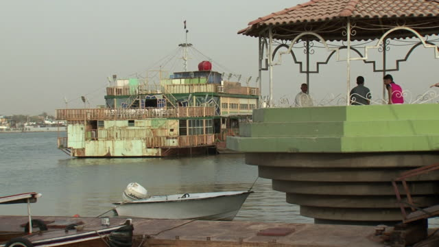 stockvideo's en b-roll-footage met 20th jul 2009 ws pan shat al arab area moored boat and two men in gazebo / basra iraq - gazebo